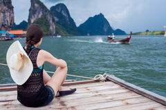 Girl in hat sitting on pier and enjoy view. Young woman in Thailand, back. Stock Photos