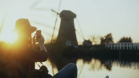 Girl in hat sitting on sunset rural lake pier. Tourist woman takes a photo of old Dutch windmill with smartphone. 4K. stock footage