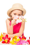 Girl in the hat smelling a branch of pink orchids Royalty Free Stock Photo