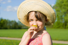 The girl in the hat smelling a flower Stock Image