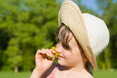 The girl in the hat smelling a flower Stock Images