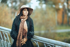 Girl in hat standing on the bridge. Beautiful brunette girl in a hat and coat standing on the bridge and looks afar Royalty Free Stock Images