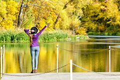 Girl in hat standing on the dock with a raised hand. Autumn, sunny. Back view Royalty Free Stock Photography