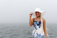 Girl in hat standing in the misty sea Royalty Free Stock Images