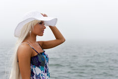 Girl in hat standing near the misty sea Stock Image