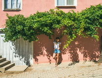 Girl in hat standing near pink wall in Turkish village Royalty Free Stock Photos