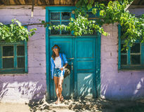 Girl in hat standing near purple wall in Turkish village Royalty Free Stock Photos