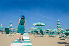 Girl in hat stands with her back on the seaside path. Stock Photos