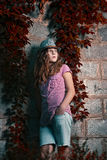 Girl in a hat stands next to the with wild grapes Royalty Free Stock Photography
