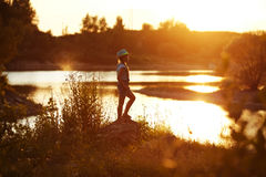 Girl in hat stands on the river bank at sunset Royalty Free Stock Photos