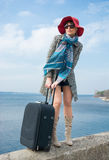 Girl in a hat and with a suitcase in front of the sea Stock Photography