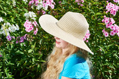 Girl with hat in summer garden Stock Images