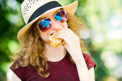 A girl in hat with sun glasses bitten off hamburger stock photography