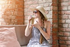 Girl in a hat and sunglasses drinks latte in a street cafe. Travel and Leisure Stock Photos