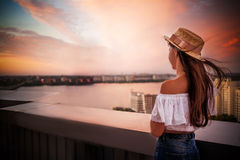 Girl in hat at sunset with flying hair royalty free stock photo