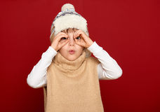 Girl in hat and sweater look through binoculars on red background Royalty Free Stock Photography