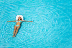 Girl with hat swimming in crystal-clear pool Stock Photography