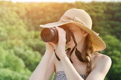 Girl in hat takes pictures against the background of green fores. T. Side view Royalty Free Stock Photography