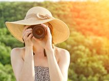Girl in hat takes pictures against the background of green fores Stock Photos