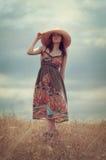 Girl in the field. Girl in a hat walking in a field Royalty Free Stock Image