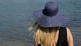 Girl with a hat watching the peaceful surface of the water, until her hair flying in the wind,view from the back