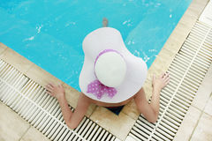 Girl in a hat in the water pool Royalty Free Stock Image