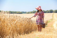 Girl in hat on wheat field Stock Images