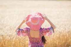 Girl in hat on wheat field Royalty Free Stock Photo