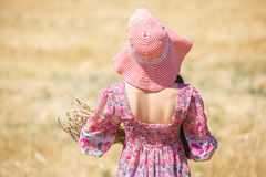 Girl in hat on wheat field Stock Photography