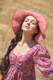 Girl in hat on wheat field Stock Photos