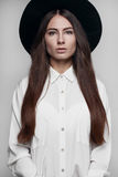 Girl in the hat on a white background. Girl with long hair in a hat on a white background and a white blouse Royalty Free Stock Image