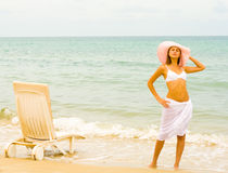 Girl in hat and white long skirt on a beach Stock Photos