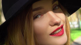 Girl in hat with wide brim and with red lips. Young beautiful girl in hat with wide brim and with red lips looking at the camera and smiling outdoors royalty free stock images