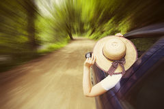Girl with hat in the window of the car Stock Images
