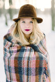 Girl in the hat wrapped in a blanket Royalty Free Stock Photos