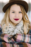 Girl in the hat wrapped in a blanket Stock Photography