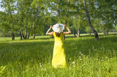 Girl in a hat and a yellow dress costs a back in the wood in the summer. The girl in a hat and a yellow dress costs a back in the wood in the summer Stock Photography