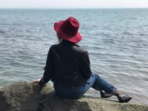 The girl in the hat. You can watch the sea endlessly. I often travel, I dress my hat, take a backpack and forward - for new impressions Stock Images