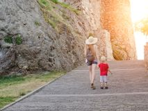 Girl in a hat with a young son walking near the walls of the fortress, sunlight. Back view Stock Photography