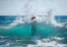Young woman in bikini unexpected flooded with big wave royalty free stock photo