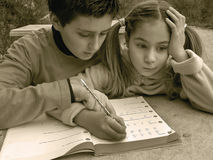 Girl have a math problems. The boy - brother helping the girl - sister (best friends) to write math homework. Her face was worried and did not clear her homework Stock Photos