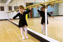 Girl having ballet lesson. A little girl standing at the mirror wall of ballet classroom Royalty Free Stock Photo