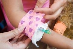 Girl having bandage put around catheter Royalty Free Stock Image