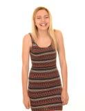 Girl having big laugh. Portrait of blonde teenage girl wearing smart patterned dress having a big laugh, white background Stock Photo