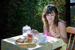 Girl having breakfast in the garden. Smiling girl having breakfast in the garden Royalty Free Stock Photo