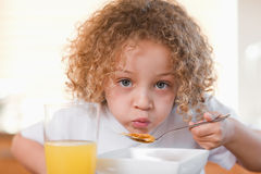 Girl having breakfast in the kitchen Stock Image