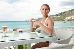 Girl having coffee break in an ocean view cafe Royalty Free Stock Photos