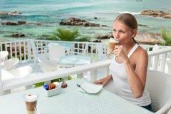 Girl having coffee break in an ocean view cafe Stock Photography