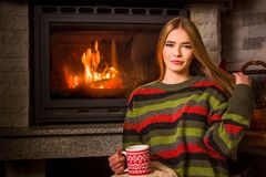 Girl having a cup of tea by the fireplace Stock Images