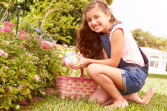 Girl Having Easter Egg Hunt In Garden Stock Photos